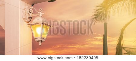 Lantern lit at sunset in a sky full of clouds