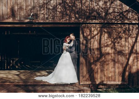 Rustic Wedding Couple Posing And Hugging In Sunlight At Background Of Wooden Wall In Country Barn. W