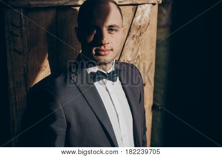 Stylish Groom Portrait In Sunlight On Background Of Wooden Wall In Country. Rustic Wedding Concept I