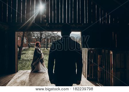Stylish Groom Walking To His Beautiful Bride In Sun Light In Wooden Barn. Rustic Wedding Concept, Sp