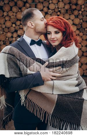 Stylish Groom And Happy Bride In Blanket Kissing On Background Of Wooden Firewood Wall. Rustic Weddi