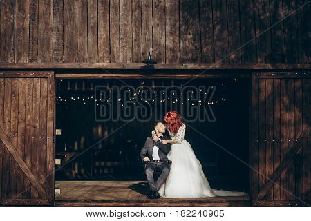 Rustic Wedding Couple Posing And Hugging At Background Of Wooden Barn With Retro Lights, Space For T