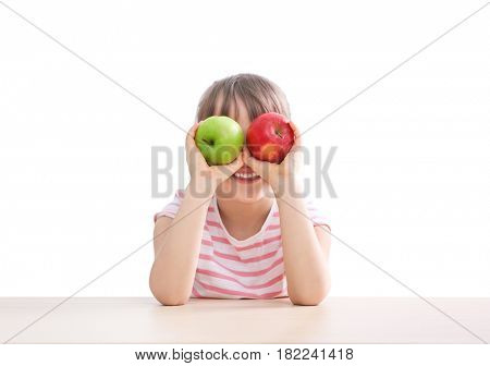 Happy schoolgirl sitting with apples at table on white background