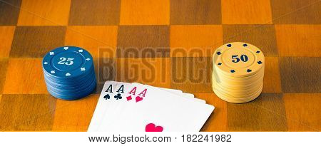Four aces and poker chips on the chessboard fascinating and popular table games all over the world a plastic reward for winning