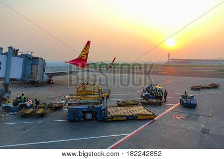 Beijing China-May 19 2016: The aircraft of Hainan Airlines is parked at the aerobridge of Beijing capital international airport with ground handling equipment and staffs around