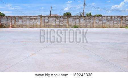 Background cement floor in car park the bottom of the image is the copy space The top is a wall of blocks and clouds in the blue sky. Be hide of the wall landscape are electric poles and roofs.