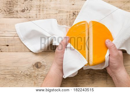 Top view on cut cheese head in yellow vacuum pakage in man's hands on wooden board. Serving French homemade cheese. Food concept