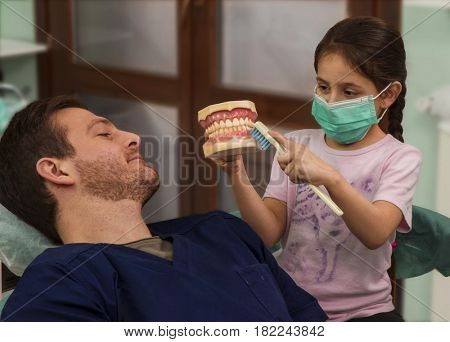 Little girl kid teach the dentist doctor how to use teeth brush using artificial teeth's in clinic studio. Little doctor.