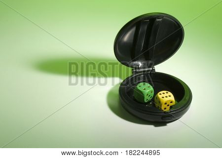Dice in Compact Case on Green Background