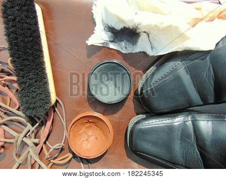 black shiny shoes with shoe polish, a brush, a cloth and shoelaces