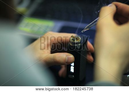 Vape After-sales Service Of The Electronic Cigarette. Male Hands Add Liquid With Nicotine For Vaping