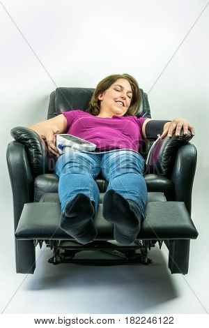 Pretty middle-age woman laying in black leather recliner armchair. Checking blood pressure using portable blood pressure machine.