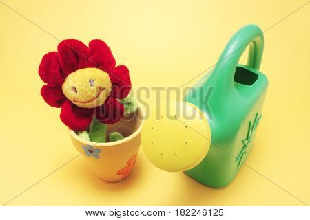 Toy Sunflower and Watering Can with Yellow Background