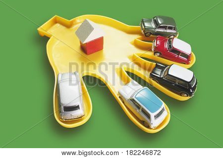 Plastic Hand with Toy Cars on Green Background