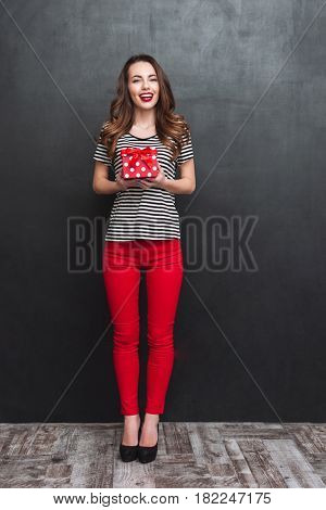 Full length portrait of a happy woman holding a gift box and looking at the camera over black background. Vertical image