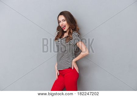 Smiling pretty woman posing sideways and looking at the camera over gray background