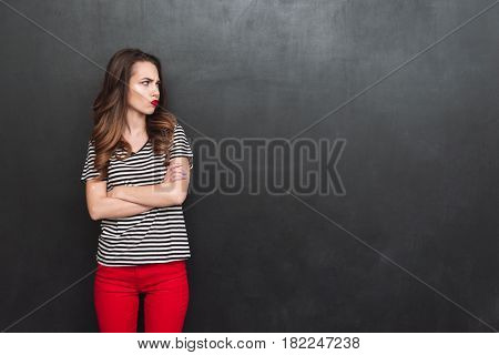 Displeased woman with crossed arms standing in studio and looking away over black background
