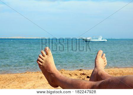 man foots on beach near turquoise sea