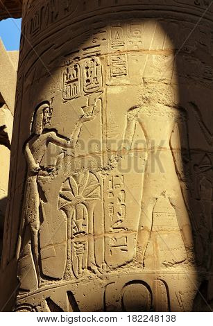 column in karnak temple with ancient egypt images and hieroglyphics
