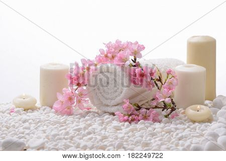 Branch Pink cherry flower and rolled towel ,candle,on pile of white stones,