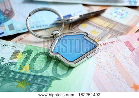 Savings concept. Key with trinket on money