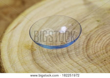 A soft contact lens lies on a wooden surface
