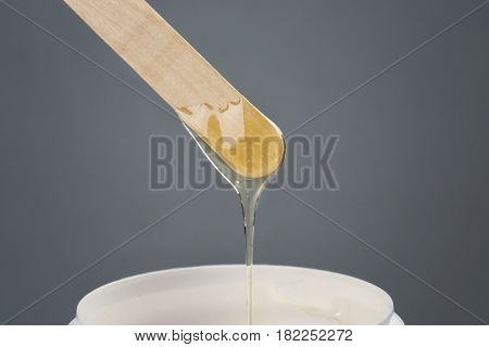 Wooden stick with sugaring paste on grey background