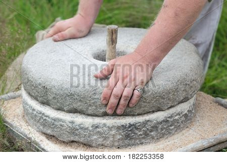 The ancient Quern stone hand mill with grain. The man grinds the grain into flour with the help of a millstone. Men's hands on a millstone. Old grinding stones turned by hands poster