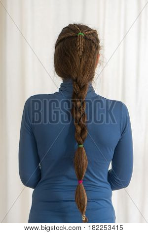 English plait renaissance hairstyle for long hair. Traditional plait style modelled by girl with very long golden hair