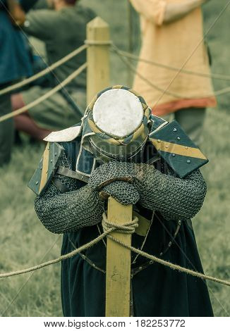 RITTER WEG MOROZOVO APRIL 2017: Festival of the European Middle Ages. Weary knight in helmet and chainmail resting after battle bending his head.