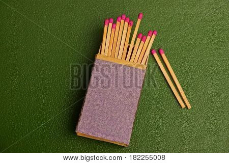 Box of matches with matches on a green background