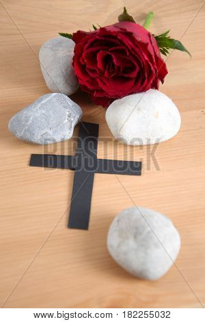 a funeral card - a black ribbon and stones