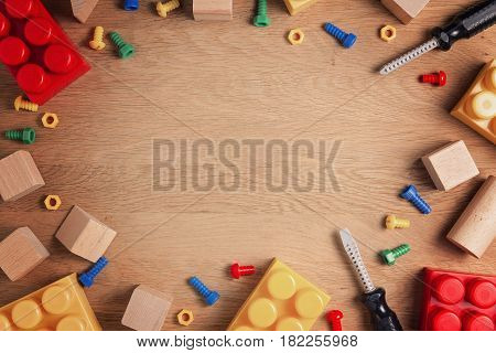 Boys toys frame background. Colorful toy tools, construction blocks and cubes on wooden table. Top view. Flat lay. Toned picture