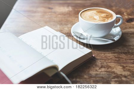 Open notebook with cup of coffee on wooden table.