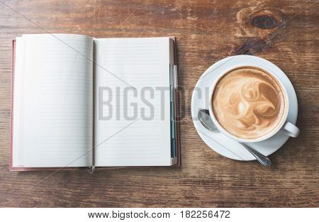 Top view of Open notebook with cup of coffee on wooden table.