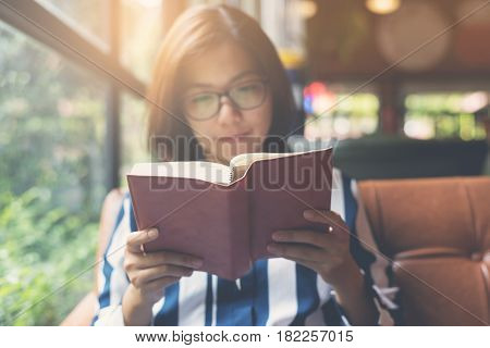 Focus on book. Relaxed Asian Woman reading a book. Happiness copy space.