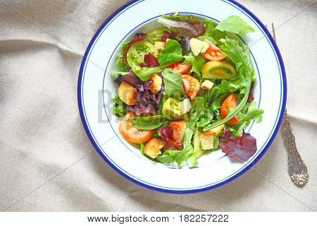 Salad with miniature heirloom tomatoes mixed young lettuces and croutons with copy space