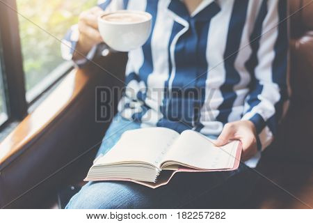 Focus on book. Woman holding a cup of coffee and notebook. Girl reading a book on leather sofa.