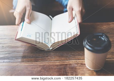 Focus on book. Woman holding notebook with a cup of coffee on wooden table.