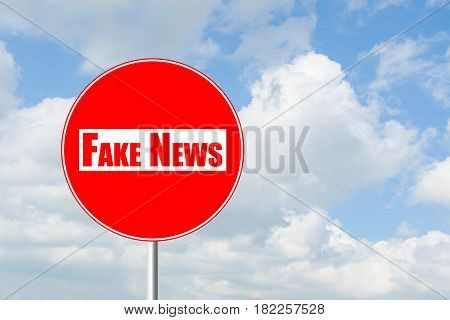 No entry for fake news prohibitory traffic sign against blue sky and white clouds