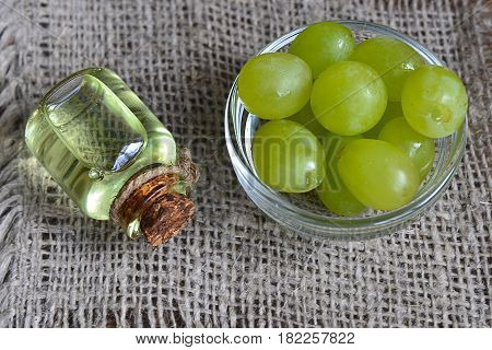 Grape seed oil in a glass jar and fresh green grapes.Bottle of organic grape seed oil for spa and bodycare.Spa,Bio,Eco products concept.Selective focus.