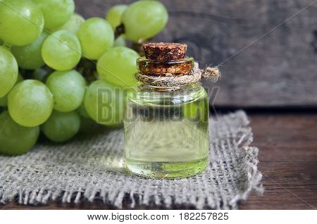Grape seeds oil in a glass jar and fresh grapes on old wooden background.Bottle of organic grape seed oil for spa and bodycare.Spa,Bio,Eco products concept.Selective focus.