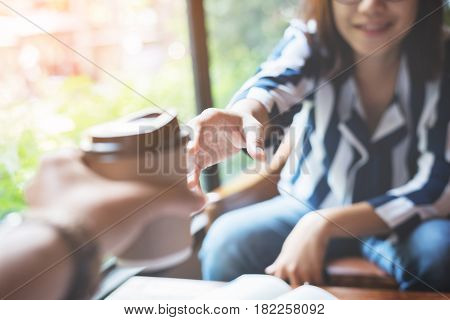 Man handing a cup of coffee to a asian woman.