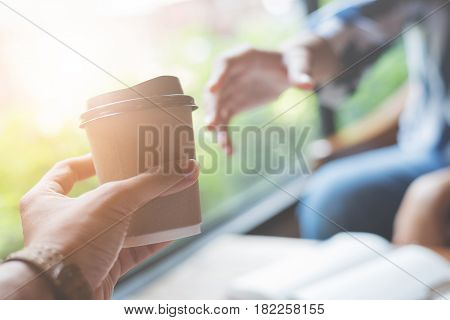 Man handing a cup of coffee to a woman.