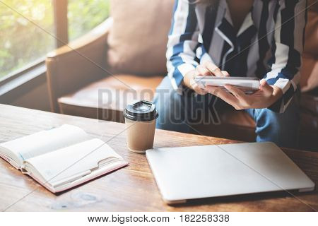 Woman sitting on leather sofa and using tablet for her working. Laptop notebook and cup of coffee on wooden table.