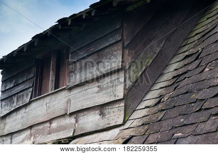 Old derelict wooden house roof detail with wear