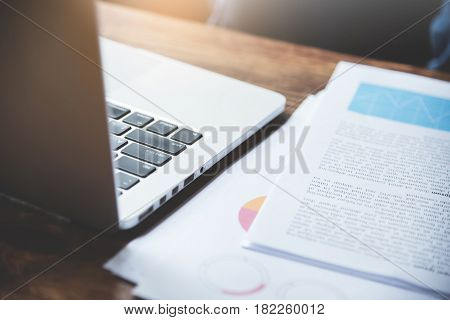 Closeup of laptop with graph financial diagram documents on wooden table.