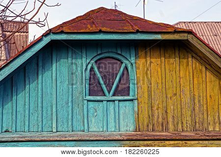 Old colored wooden loft with a small window