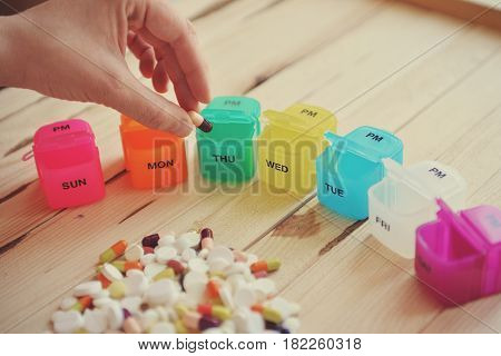 Pill box with variety of pills and supplement. A plastic weekly pill box. Daily pill box with medications and nutritional supplements.