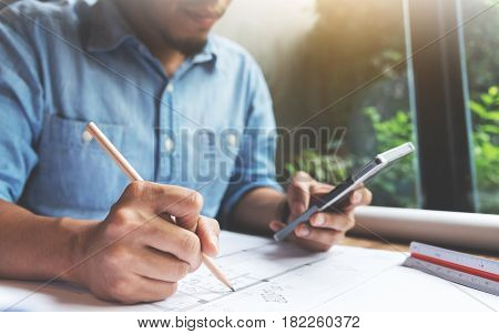 Close Up Asian man hand writing on document papers with pencil and holding cell phone. Freelance designer drawing his job.